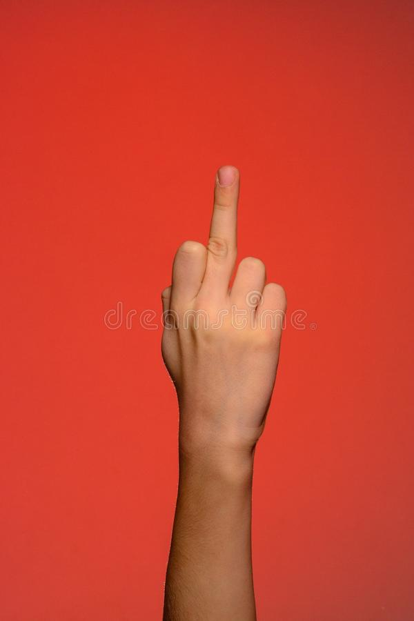 Human hand showing an obscene gesture with a middle finger isolated on a red background royalty free stock images
