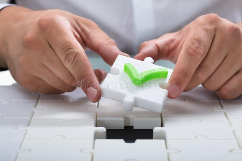 Human hand solving jigsaw puzzle stock photography