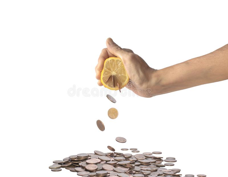 Human hand squeezing a lemon from which coins come out. Coins falling into heap of money, isolated on a white background royalty free stock images
