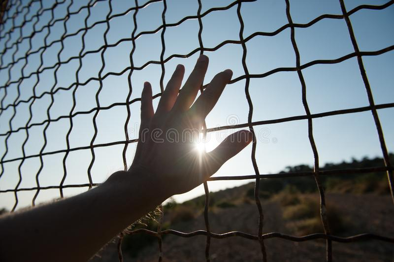 Human hand touching fence cage in jail and illegal immigration on sunset stock photos
