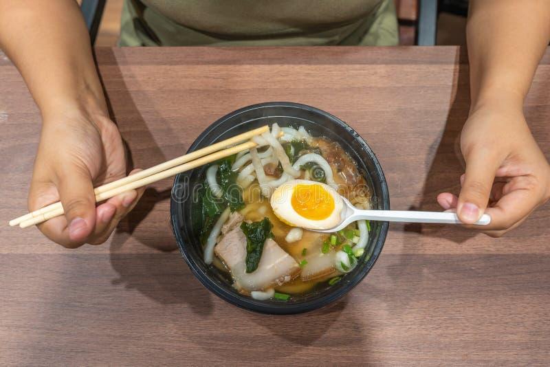 hand holding chopsticks for eating ramen noodles stock