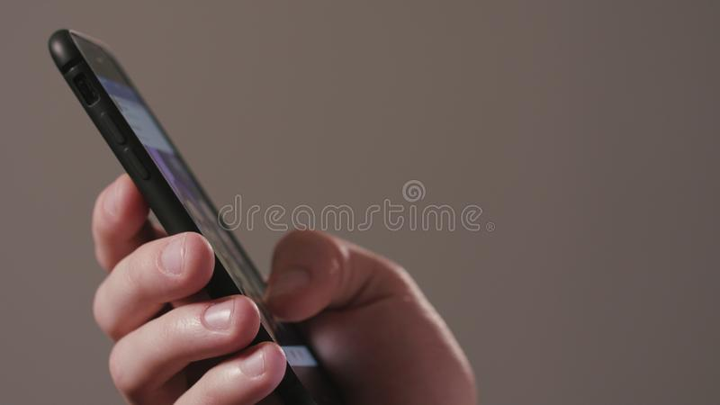 A Hand Using a Smartphone Against a Dark Background stock image