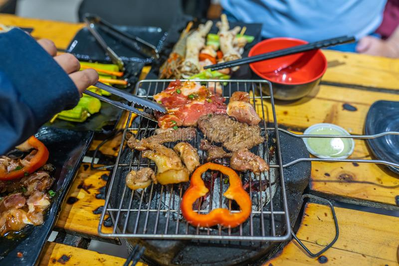 Human hand using tongs and grilling barbecue meat slices. Human hand using tongs and grilling delicious barbecue meat slices royalty free stock photography
