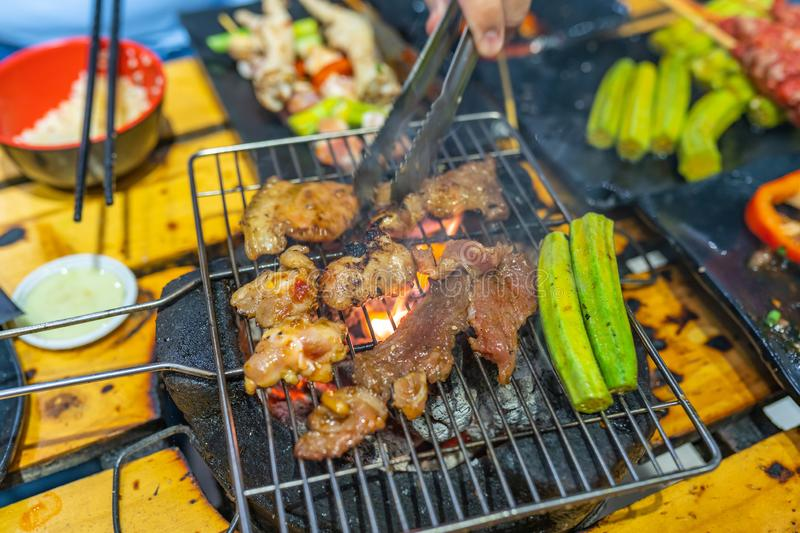Human hand using tongs and grilling meat on charcoal stove. Human hand using tongs and grilling marinated meat on charcoal stove royalty free stock photos