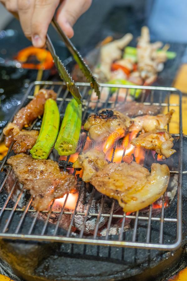 Human hand using tongs while grilling meat on flaming stove. Human hand using tongs while grilling meat on flaming charcoal stove stock images
