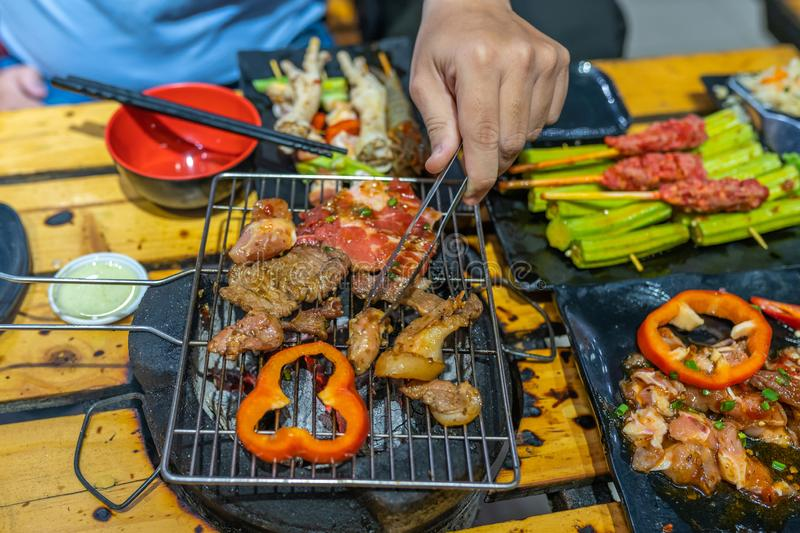 Human hand using tongs while grilling meat and bell pepper. Human hand using tongs while grilling meat slices and bell pepper stock photography