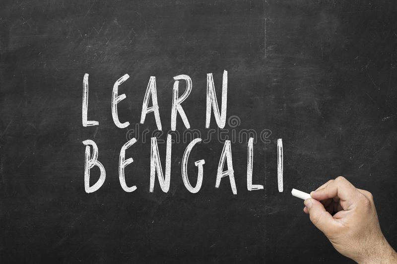 Human hand writing text on blackboard: Learn bengali.  royalty free stock images