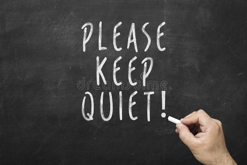Human hand writing text: Please keep quiet on black chalkboard. stock photos