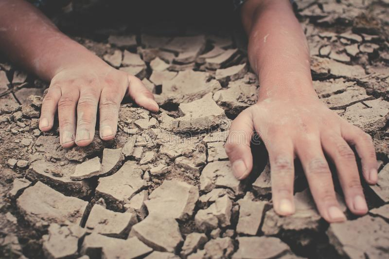Human hands on cracked dry ground. Concept drought and shortage of water crisis royalty free stock photos