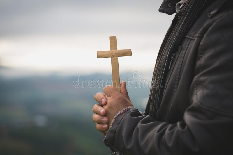 Human hands holding a cross holy and prayed for blessings from God, Amour Worship God concept. - Image stock photos
