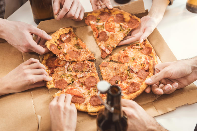 Human hands holding slices of pizza stock image