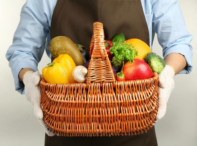 Human hands holding wicker basket with different fruits and vegetables. Closeup royalty free stock photography