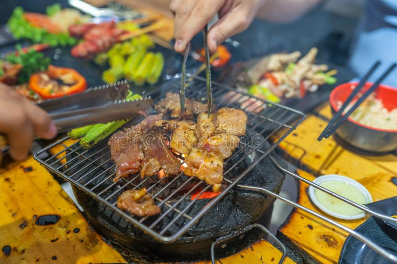 Human hands using tongs and grilling meat in barbecue party. Human hands using tongs and grilling marinated meat in barbecue party royalty free stock image