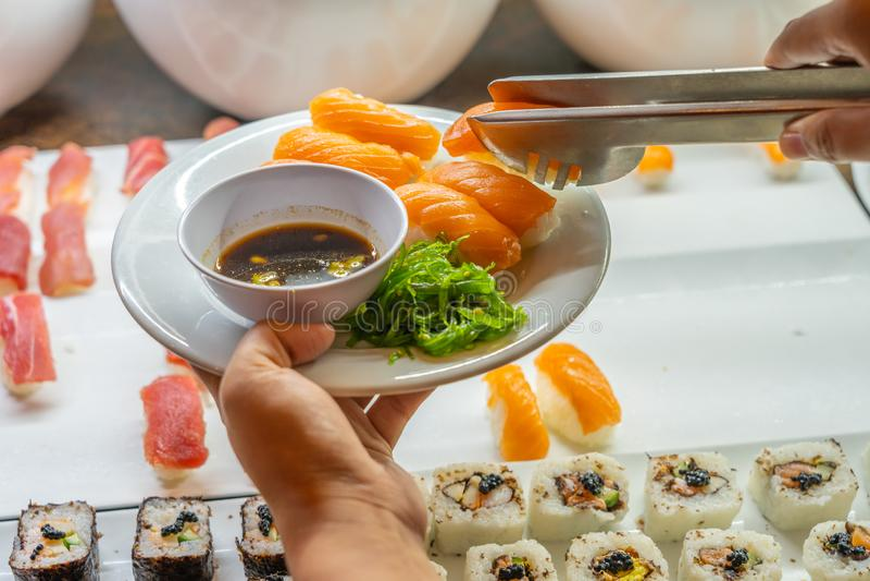 Human hands picking salmon nigiri sushi into the plate. Human hands using tongs picking salmon nigiri sushi at buffet meal royalty free stock images