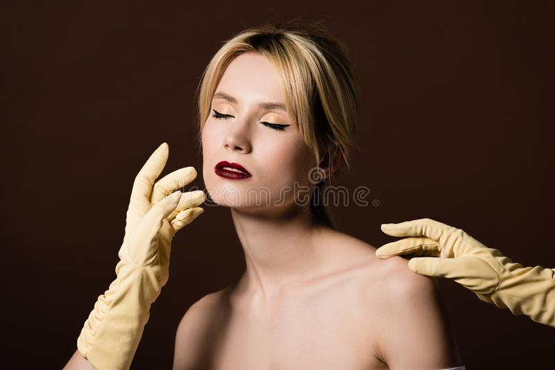 Human hands in yellow gloves touching seductive naked blonde girl. On brown stock images