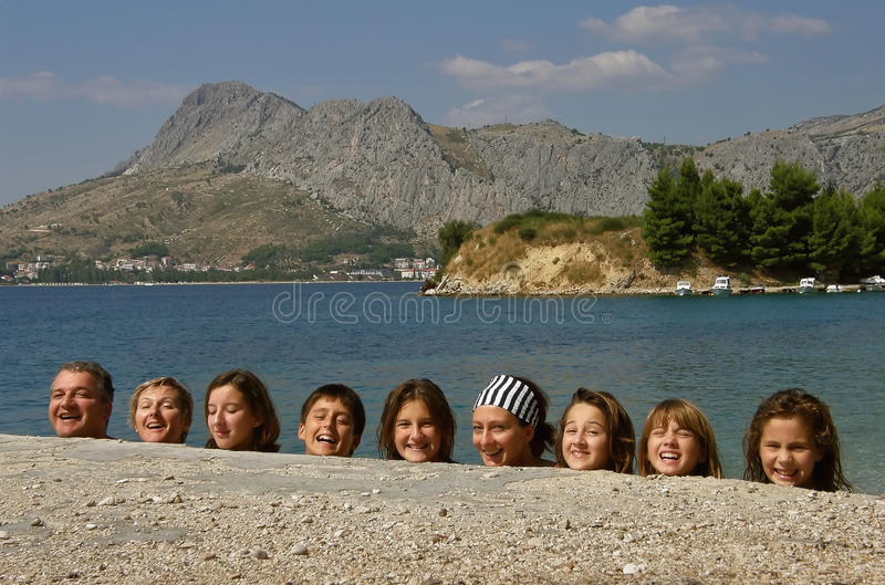 The human head happy. Big happy smiling family hidden behind the wall. On the photo you can see only smiling heads, arranged in a line near to the Adriatic Sea