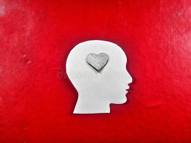 Human head thinking for love only with small paper heart stock photo
