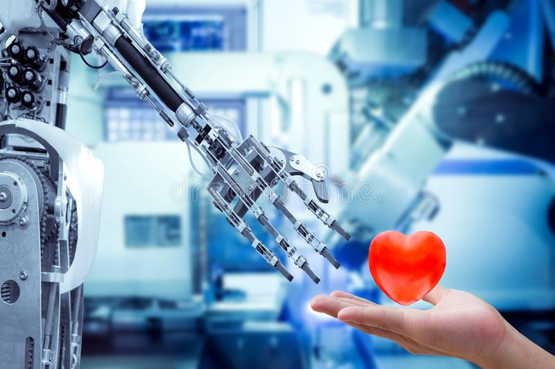 Human heart on hand send to a robot for make the robots have feelings, love, like a human. royalty free stock photography