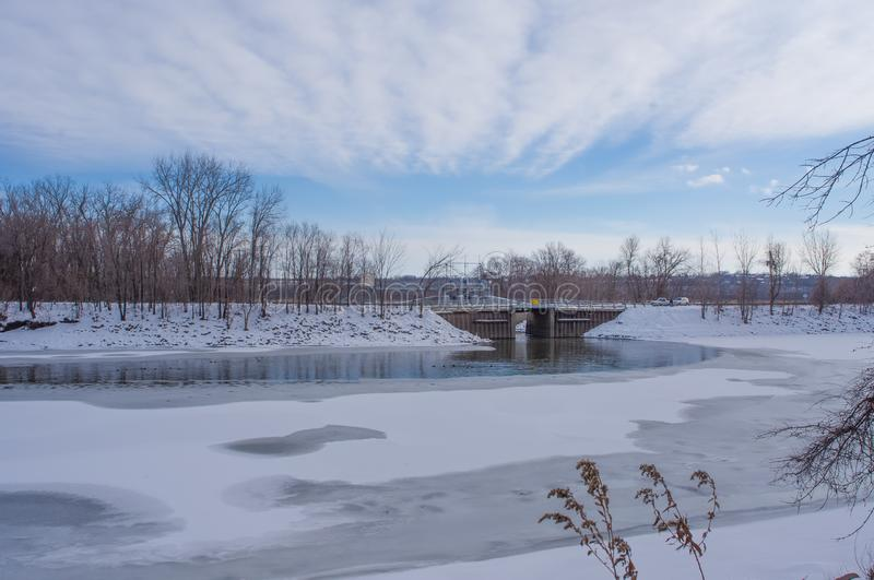 Human managed structure dam or bridge near a coal power plant - near the Minnesota River on a sunny, cold, snowy winter day.  stock images