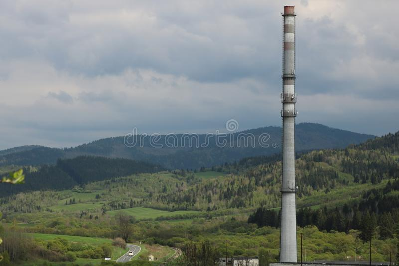 Human marks in nature. Photography of the chimney of the saw mill with the mountains in the background. Slovakia, village Polomka stock image