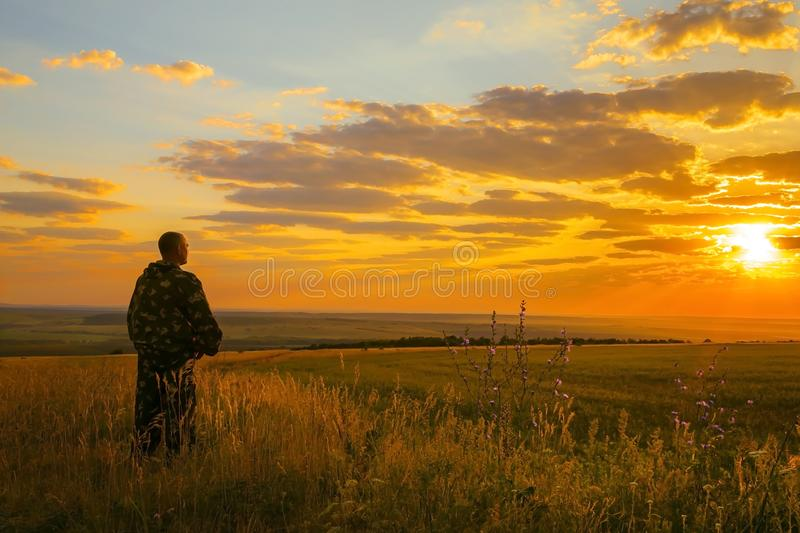 Human and nature. A European man stands in a field, looking into the distance to the horizon and enjoying the view of the stock images