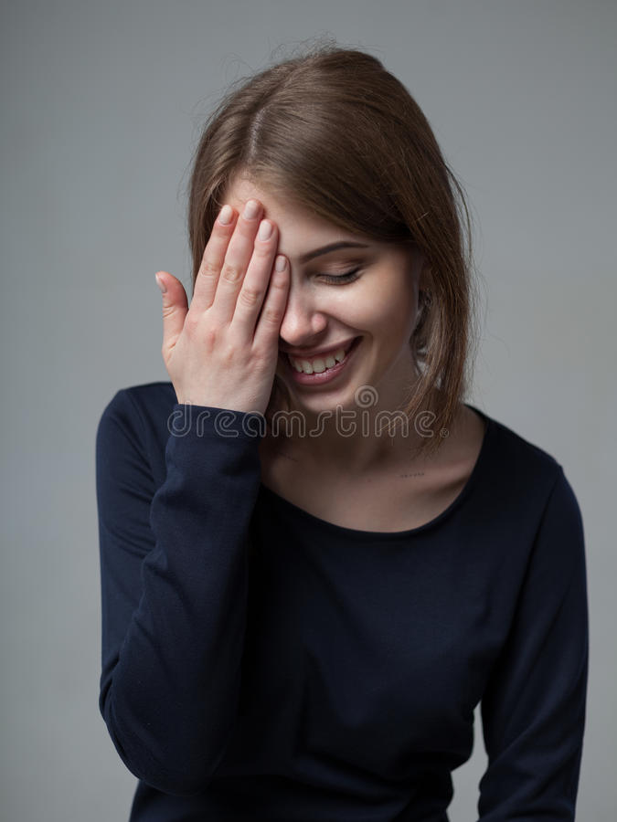 Human positive emotions and feelings. Headshot of cute attractive young European female covering open mouth with hand and closing royalty free stock photo