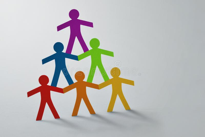 Human pyramid of colorful paper cut-out people on white background - Concept of teamwork and diversity royalty free stock images