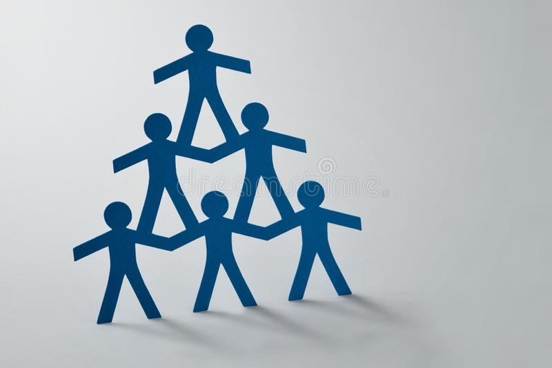 Human pyramid of paper cut-out people on white background - Concept of teamwork. Human pyramid of paper cut-out people on white background. Concept of teamwork royalty free stock photo