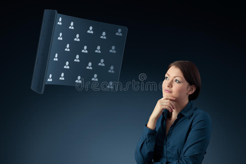 Human resources HR. Human resources female officer think about new candidates or team structure displayed on futuristic virtual screen. Marketing specialist royalty free stock photos