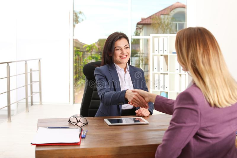 Human resources manager shaking hands with applicant during job interview. In office royalty free stock photo