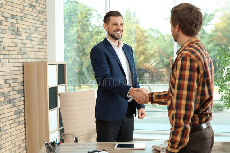 Human resources manager shaking hands with applicant during job interview. In office stock photos
