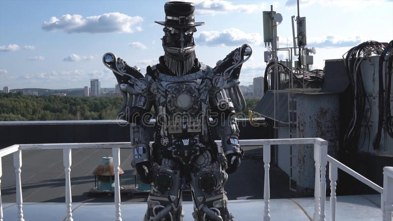 Human robot in all growth is driven by limbs on background of blue sky with clouds. Footage. Android with face and hat. Demonstrates its ability to move royalty free stock images