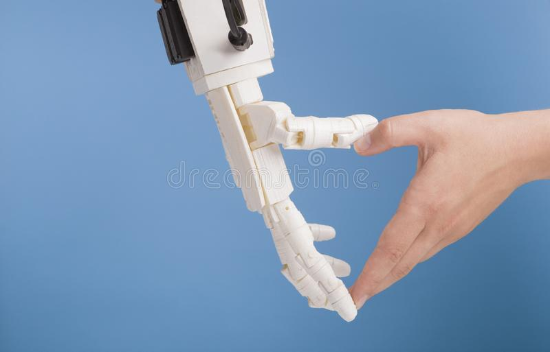 Human and robot hands making heart gesture on blue background. Unity of people and artificial intelligence. Human and robot hands making heart gesture on blue royalty free stock photography
