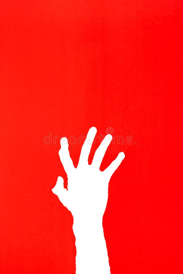 human`s hand reaching out for help on red background royalty free stock photo
