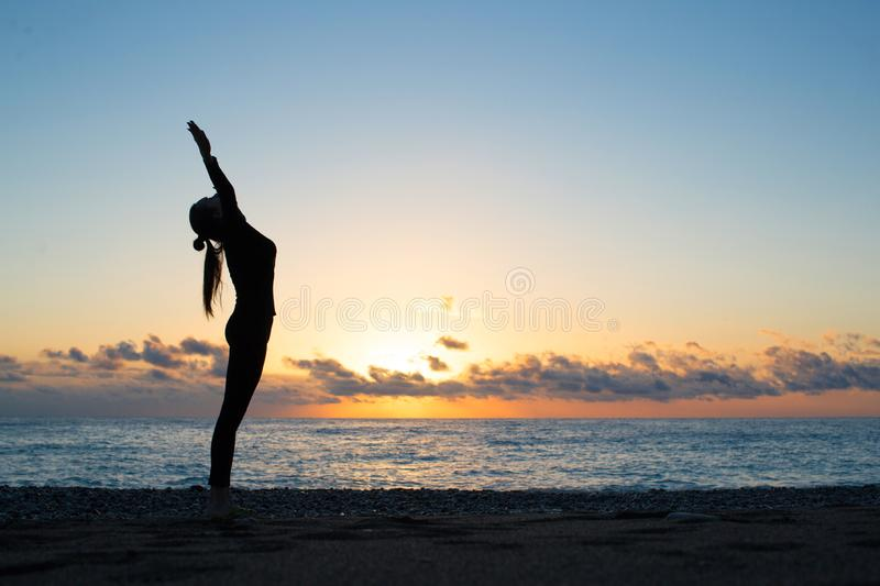 Human silhouette doing yoga on the beach at the dawn. Woman rise her hands up and greeting to the rising sun, harmony, spiritual awakening and peace concept royalty free stock image