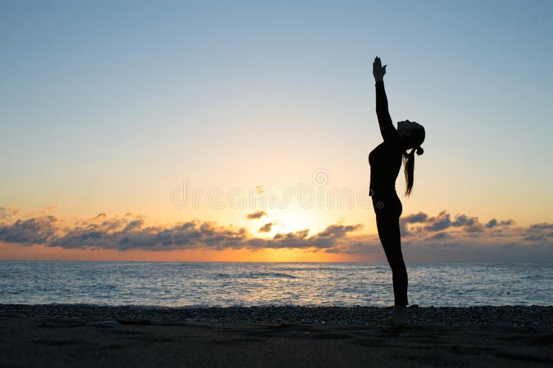 Human silhouette doing yoga on the beach at the dawn. Woman rise her hands up and greeting to the rising sun, harmony, spiritual awakening and wellness concept stock photo