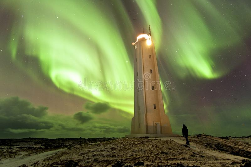 Human silhouette and lighthouse in Iceland under impresive aurora borealis spectacle royalty free stock photo