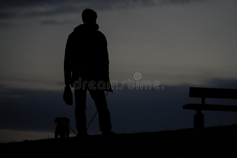 Human silhouette to the dog for a walk in the evening of the hill. Shooting location :  Chofu, Tokyo royalty free stock photo