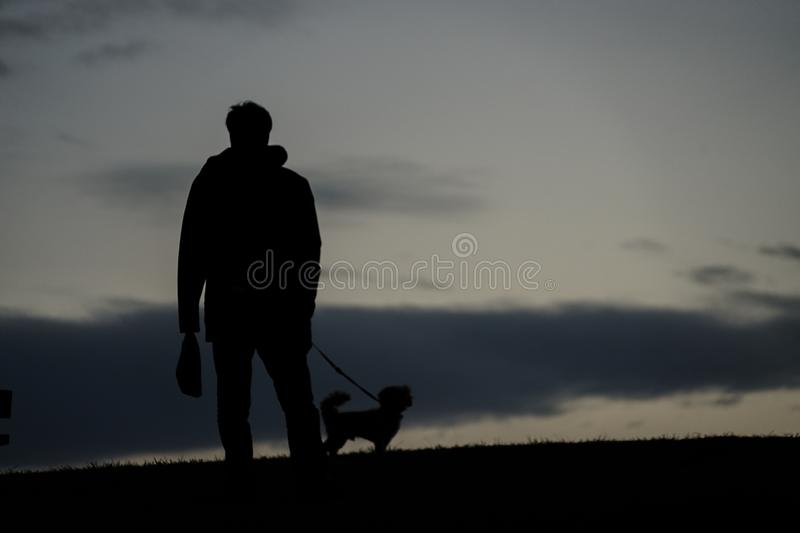 Human silhouette to the dog for a walk in the evening of the hill. Shooting location :  Chofu, Tokyo royalty free stock photos