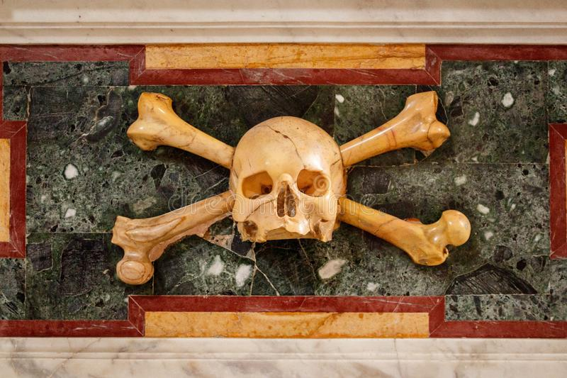Human skull with crossed bones made of marble stock image