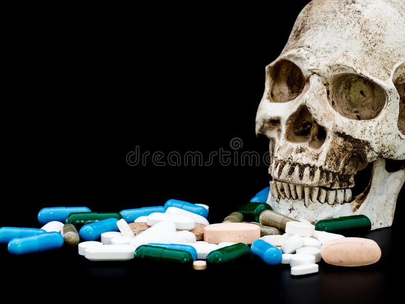 Human skull on multicolored of drug and capsule is on the black background. Close up. We are against drugs anti drugs, cure in c stock photo