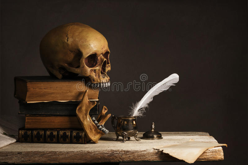 Human Skull on old Books with empty Page, Feather and Inkpot royalty free stock image