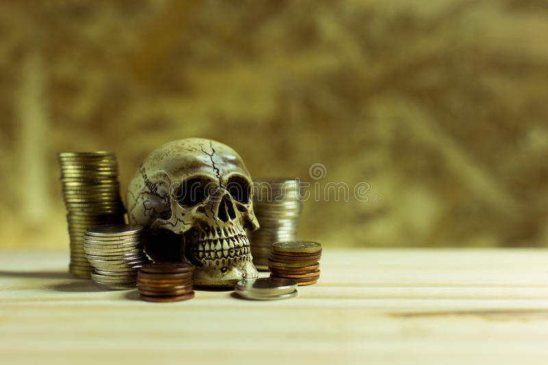 Human skull ,Pile thai coins of one bath on wood background.Concept of financial planning and savings.Vintage tone. royalty free stock photography