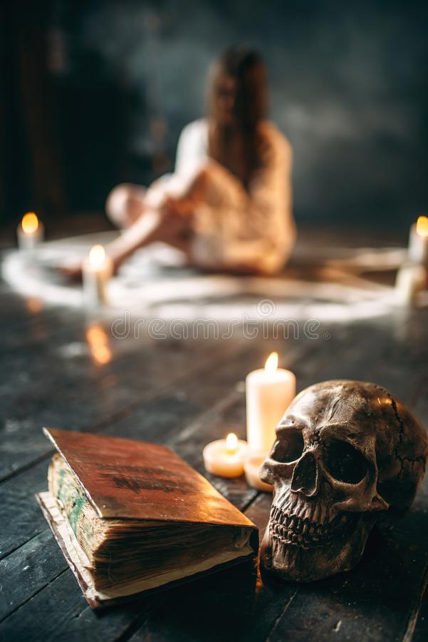 Human skull and spellbook, occultism and exorcism. Human skull and old spellbook on black wooden floor, female person in white shirt sitting in pentagram circle stock images