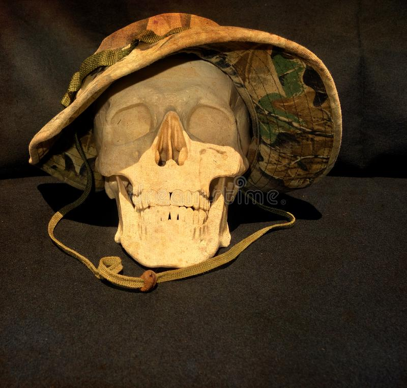 human skull wearing a Vietnam War camouflage hat royalty free stock photo