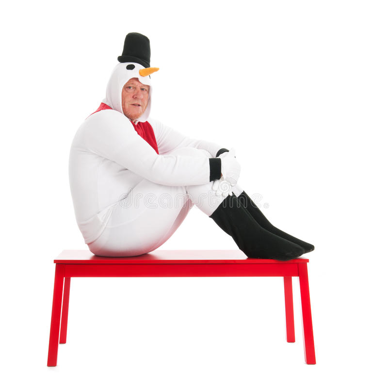 Human snowman sitting on bench. Human snowman sitting on red bench isolated over white background stock photography