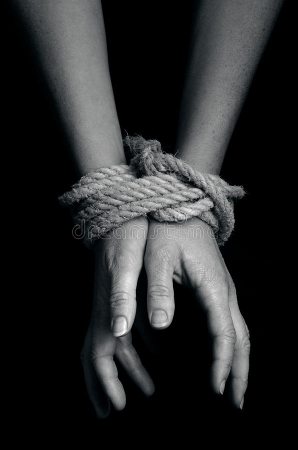 Human trafficking - Concept Photo. Hands of a missing kidnapped, abused, hostage, victim woman tied up with rope in emotional stress and pain, afraid, restricted stock images