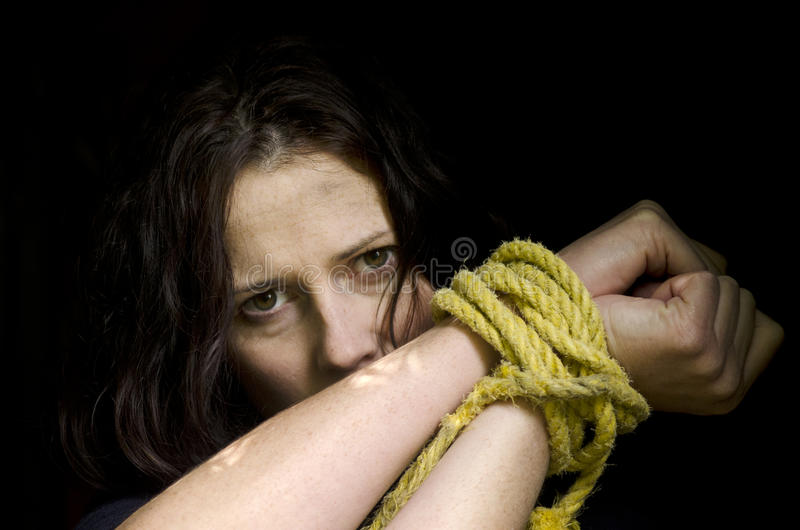 Human trafficking - Concept Photo. Missing kidnapped, abused, hostage, victim woman with hands tied up with rope in emotional stress and pain, afraid, restricted royalty free stock photos