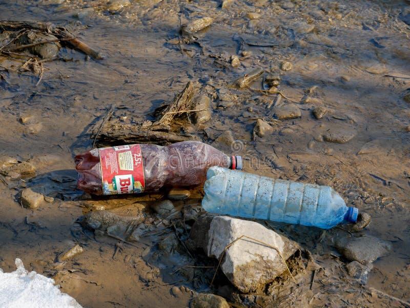 Human trash in the clean small river, conceptual image of negligence. Miercurea Ciuc, Romania-02 March 2019: Human trash in the clean small river, conceptual stock photo