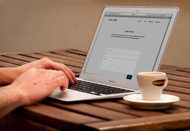 Human Using Laptop Beside Teacup on the Wooden Table stock photo